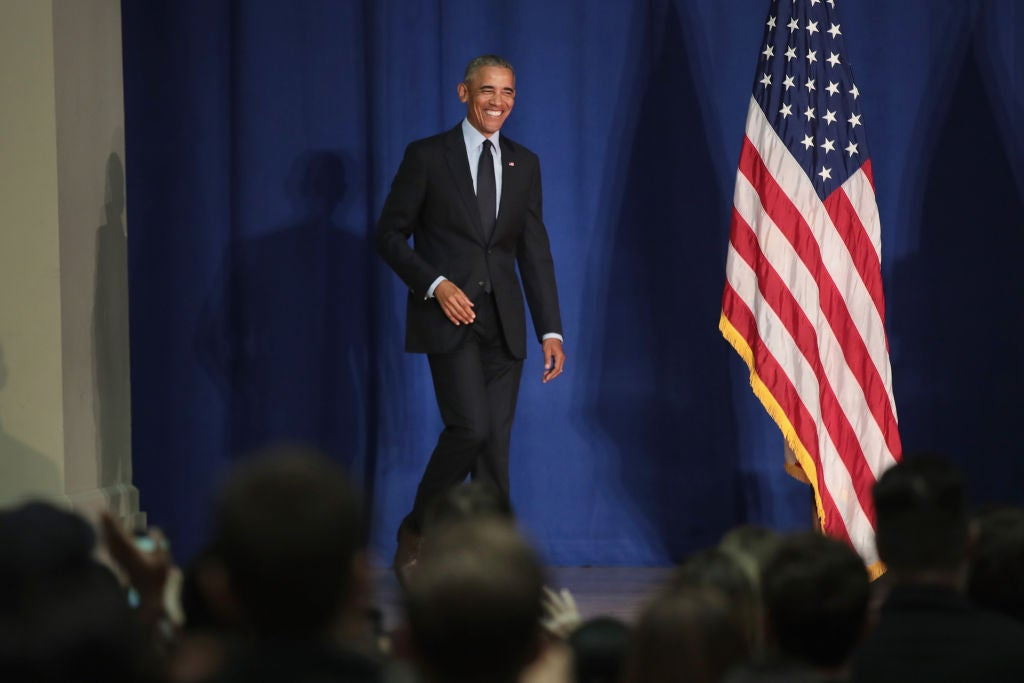 Obama smiles while walking onto a stage.