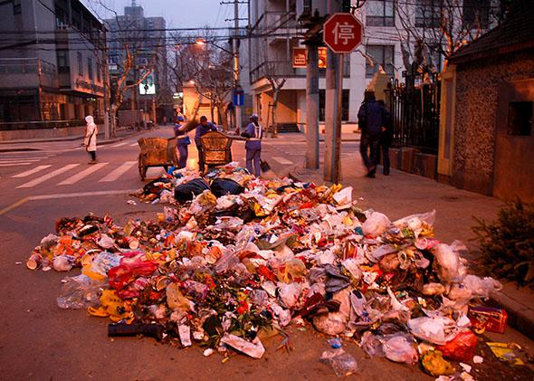 Garbage is strewn on the street as public workers collect it, Sh