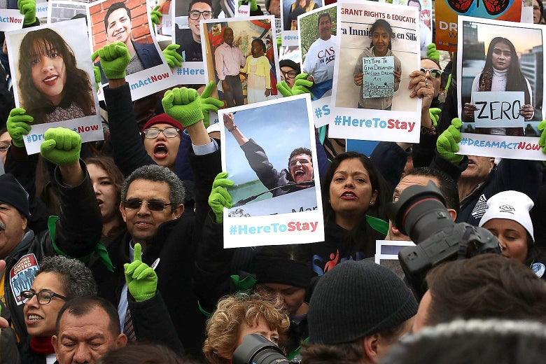A crowd of protesters holding up posters with photos of Dreamers and the hashtag #HereToStay.