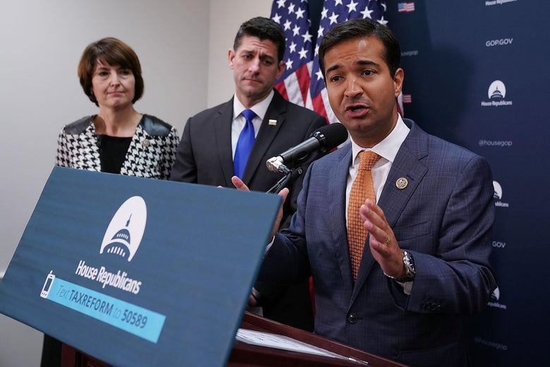 Carlos Curbelo speaks at a lectern while Paul Ryan and Cathy Rodgers stand behind him.