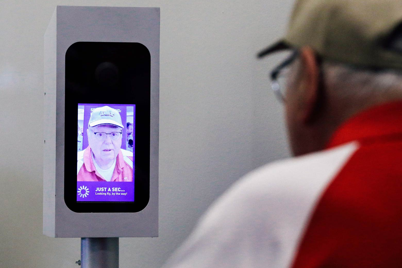 A man in a baseball cap and glasses looks into a screen on which an image of his face has been captured.