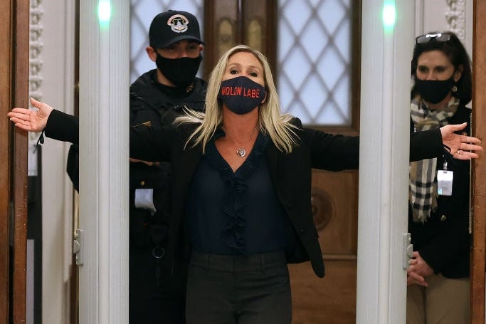 Greene, wearing black clothes and a black mask with red lettering, holds her arms out in front of a masked police officer while standing behind a metal detector.