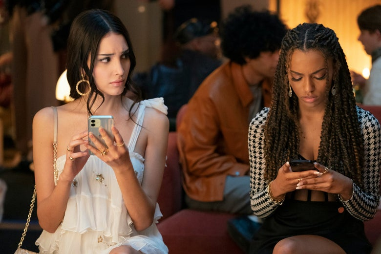 Two stylish young women on their phones at what appears to be a party