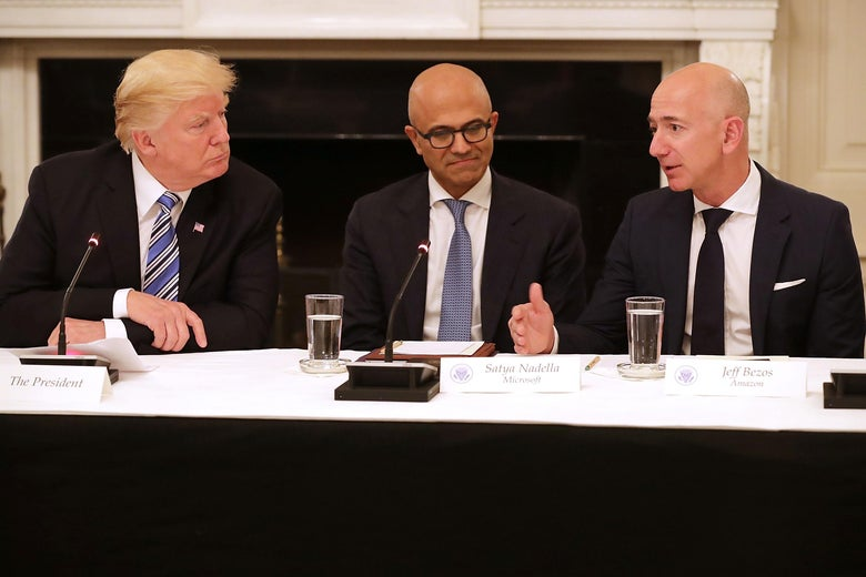 U.S. President Donald Trump, Microsoft CEO Satya Nadella, and Amazon CEO Jeff Bezos sit at a table.