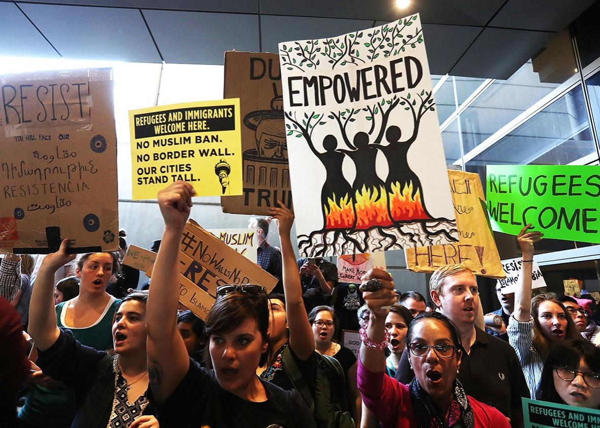 Protesters hold signs during a demonstration against the immigration ban that was imposed by U.S. President Donald Trump at Los Angeles International Airport on January 29, 2017 in Los Angeles, California.