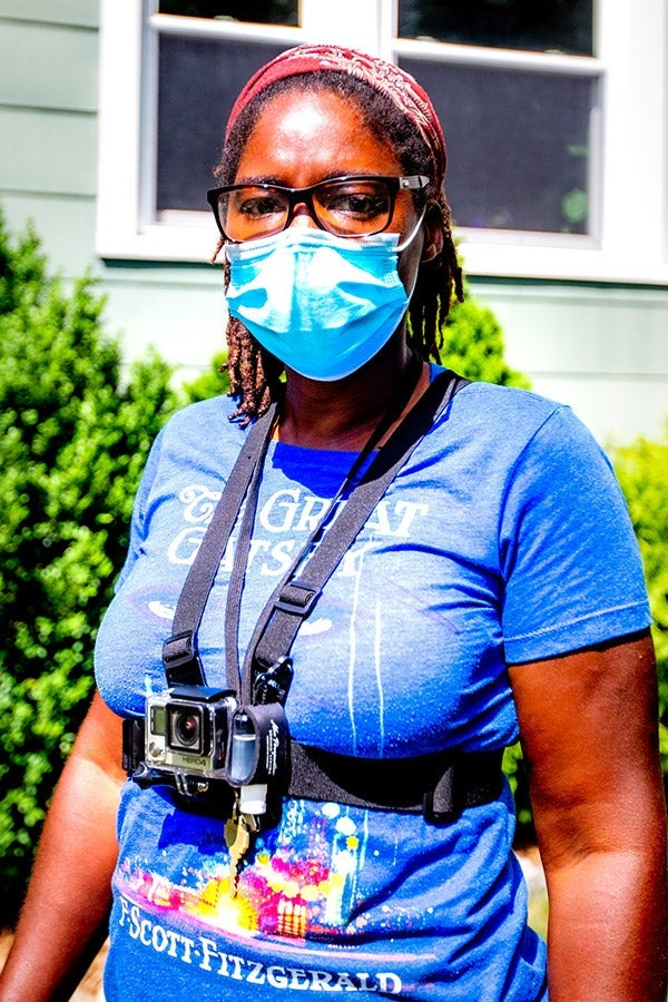 A woman in a face mask and a Great Gatsby T-shirt wears a GoPro strapped to her chest.