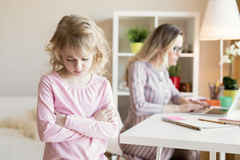 A child frowns while her mom blogs about her frowning.