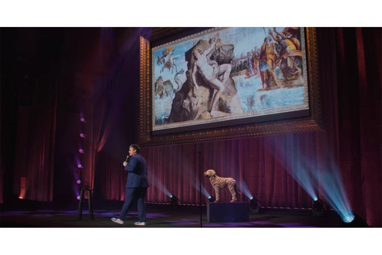 Hannah Gadsby stands in front of a projection screen displaying a fresco of Andromeda chained to her rock.