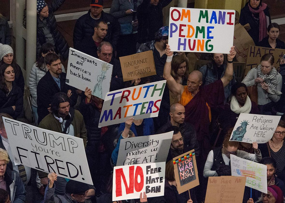 People hold up signs during a protest against US President Donald Trump's immigration rules at the Reagan National Airport in Arlington, Virginia on February 1, 2017.