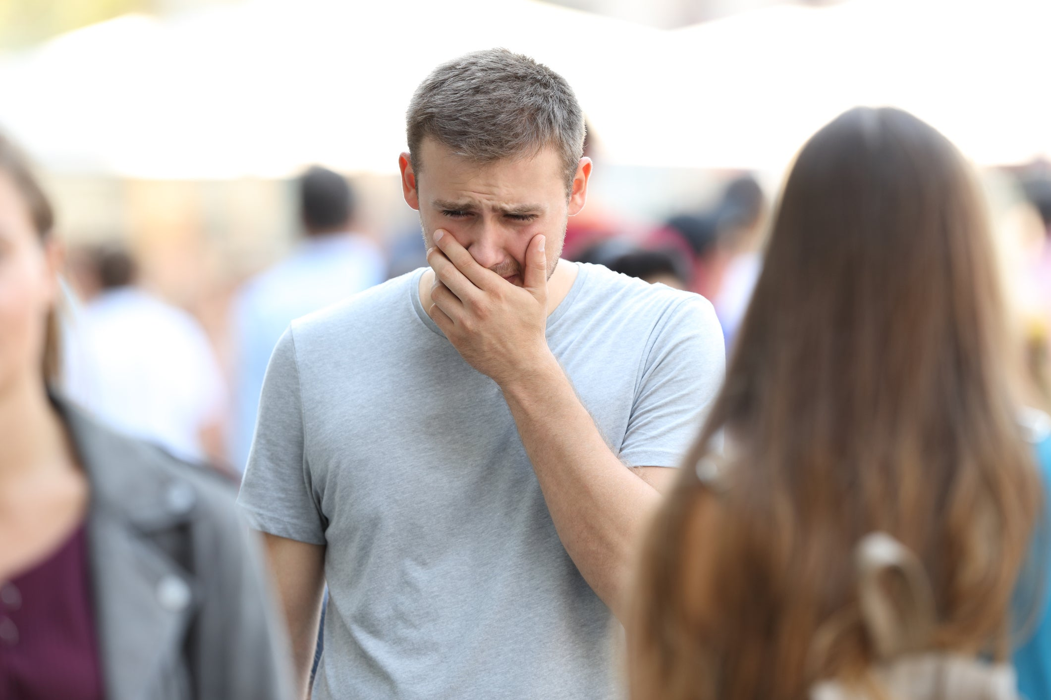 A man crying in the middle of a crowded sidewalk.