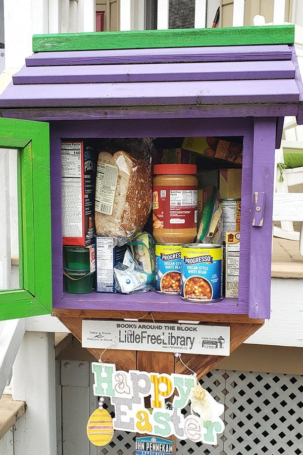 A Little Free Library filled with bread, peanut butter, and canned soup.