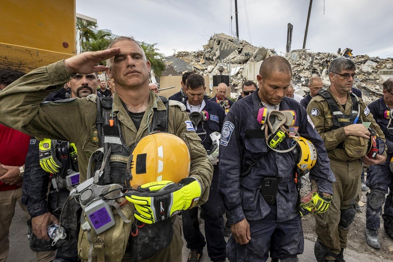 One worker salutes, as members of search and rescue teams gather with rubble in the background for a moment of silence and prayer for the victims of the condo collapse.