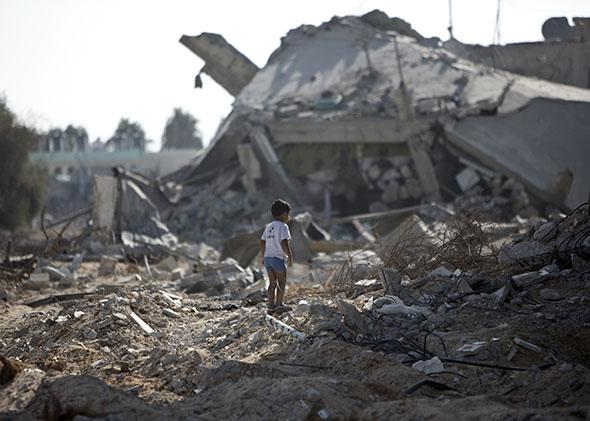 A Palestinian boy walks over debris as civilians who were displaced due to fighting between Israel's army and Hamas fighters return to check their homes in Gaza City's Shejaiya neighborhood, on Aug. 1, 2014.
