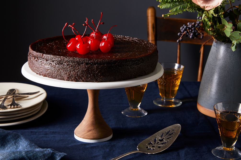 A deep black cake with bright red cherries on top.