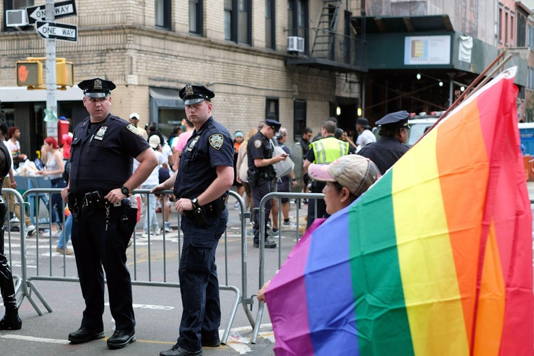 NYPD officers stand near pride flag in streets of New York.
