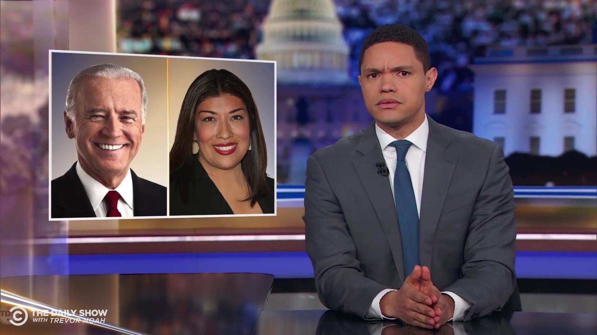 Trevor Noah at an anchorman's desk in front of photos of Joe Biden and Lucy Flores.