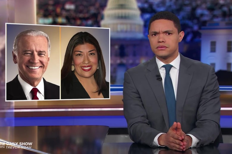 Trevor Noah at an anchorman's desk in front of photos of Joe Biden and Lucy Flores.