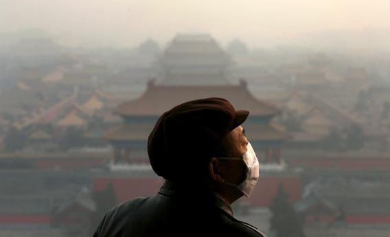 A tourist wearing a mask looks at the Forbidden City as pollution covers the city on Wednesday in Beijing, China.