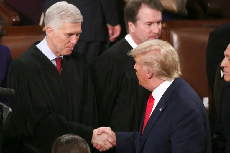 Trump shakes Gorsuch's hand while Brett Kavanaugh stands by.