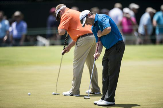 Tim Clark (R) of South Africa uses an anchored putter during practice before the US Open at Merion Golf Club
