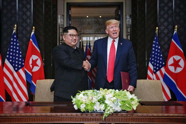 Kim Jong-un and President Trump shaking hands amid North Korean and American flags