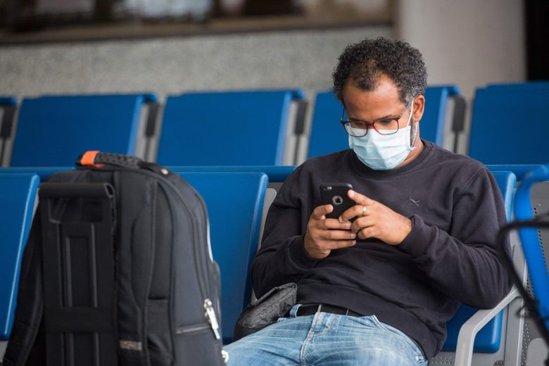 A passenger uses his mobile phone as he wears a face mask while seated.