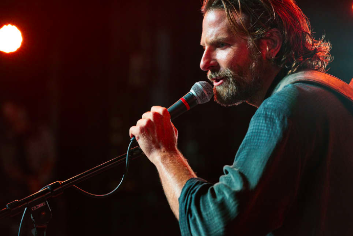 Bradley Cooper, in a blue shirt, beard, and long hair, sings into a microphone.