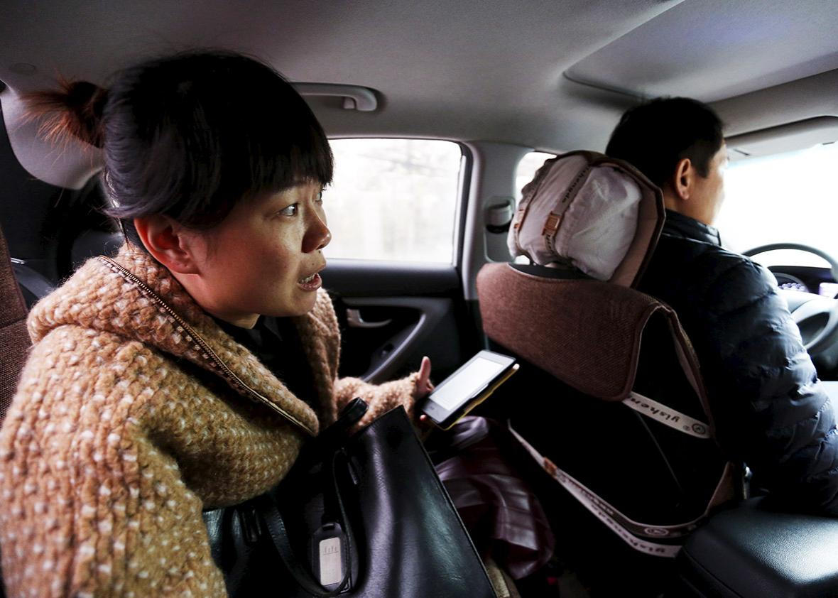 Yoko Wu instructs an Uber taxi driver en route to her office in Beijing, China, November 18, 2015. Yoko lives in the Beijing suburbs with her family and children.