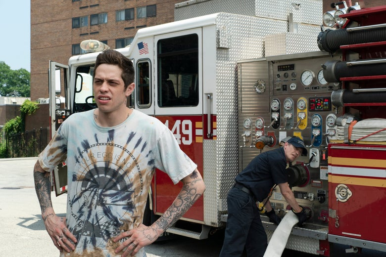 Pete Davidson, hands on hips, stands outside of a firehouse.