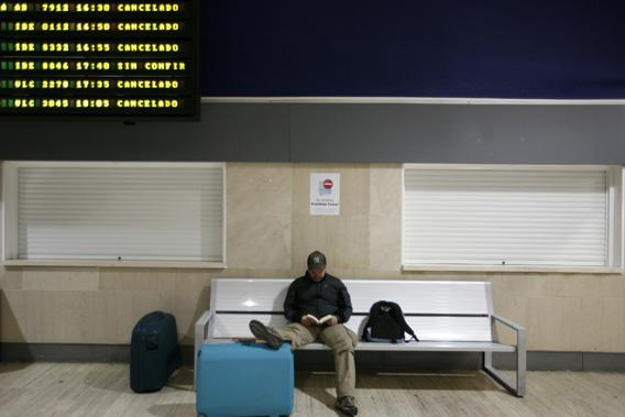 A passenger reads a book at the San Pablo Airport in Seville May 11, 2010.