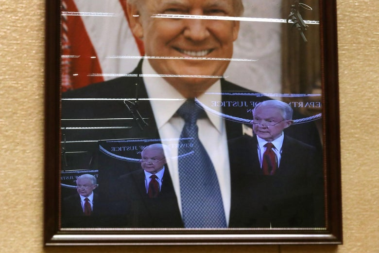 Jeff Sessions' television image is reflected in President Donald Trump's official portrait during a news conference at the Department of Justice December 15, 2017 in Washington, DC.
