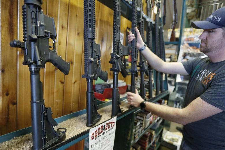 Dordon Brack, pulls a semi-automatic AR-15 off the rack, that is for sale at Good Guys Guns & Range on February 15, 2018 in Orem, Utah.