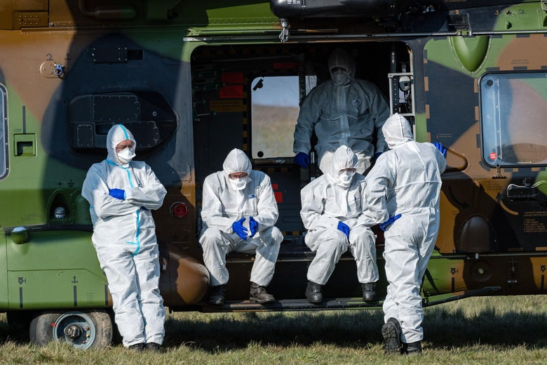 Five people in masks and protective suits are seen inside and in front of a vehicle.