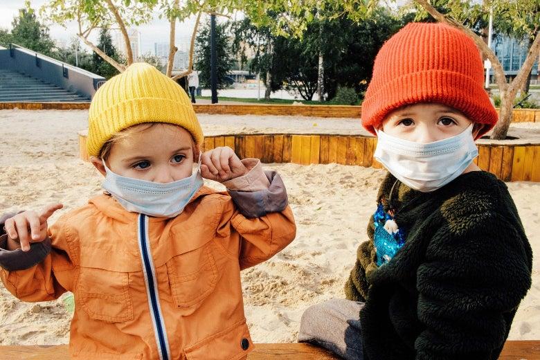 Two little kids in a sandbox wearing masks.