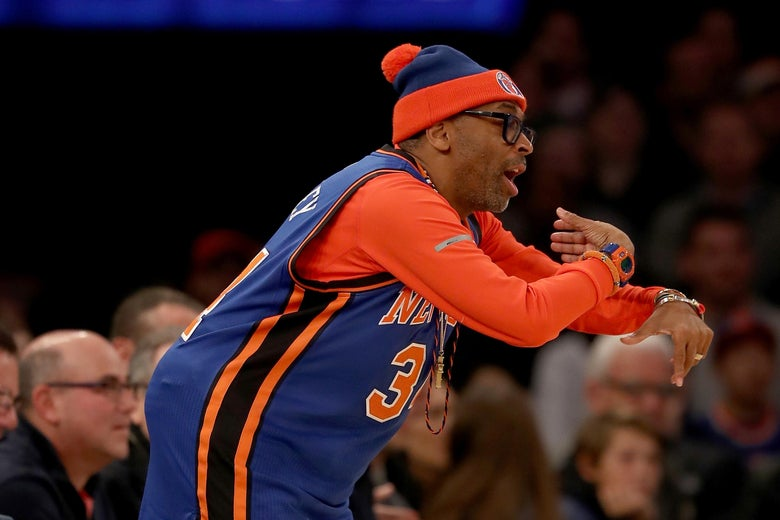 Spike Lee wearing a Knicks jersey, gesturing courtside at a game between the New York Knicks and the San Antonio Spurs in New York on Feb. 12, 2017.