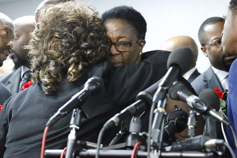 Allison Jean, Botham's mother, embraces a person with curly hair while standing in front of several microphones.