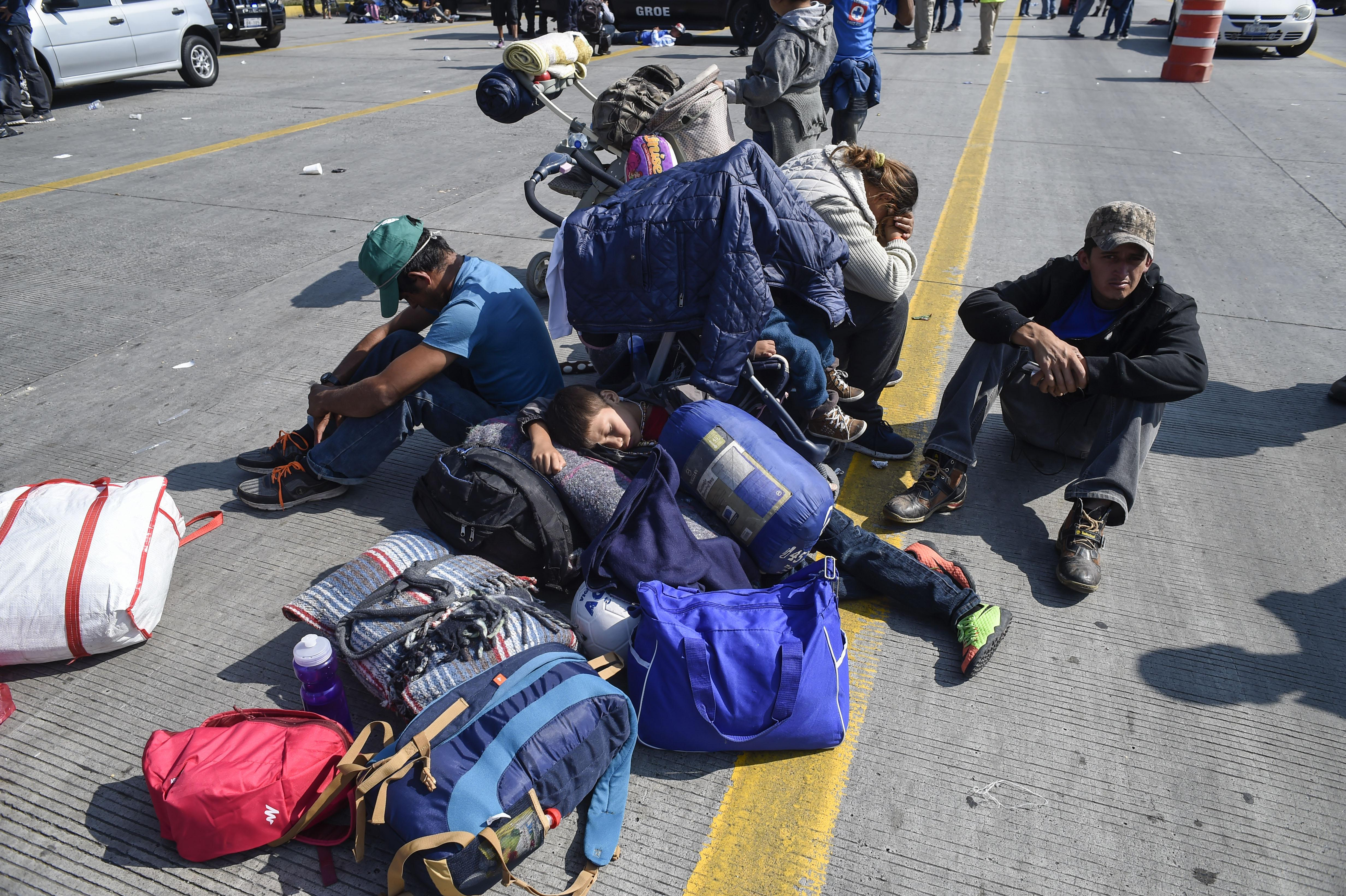 Central American migrants -mostly families with children- taking part in a caravan to the U.S., queue along the highway to get a ride to Irapuato in the state of Guanajuato on November 11, 2018.