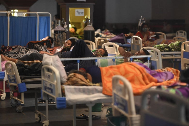 Rows and rows of COVID patients on hospital beds packed into a dimly lit room