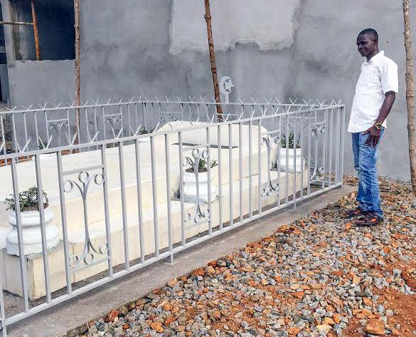 Mohamed SK Sesay standing by the grave of the late Dr. Khan, who