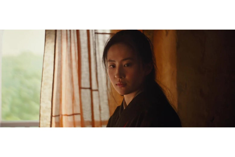 Liu Yifei in a still from Mulan; an overly-bright window and a very dark interior wall are behind her.