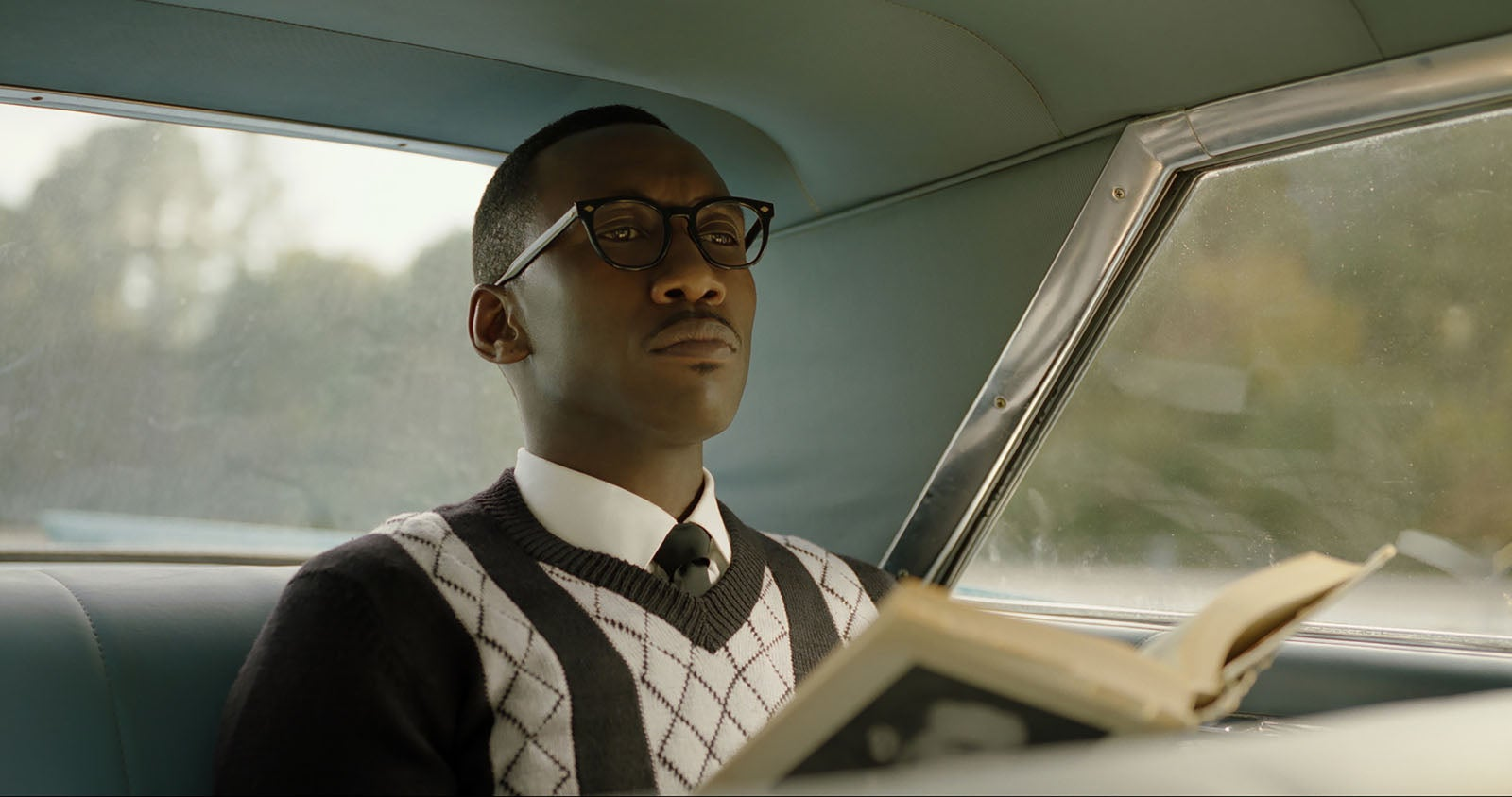 An unsmiling Mahershala Ali sits in the backseat of a car.