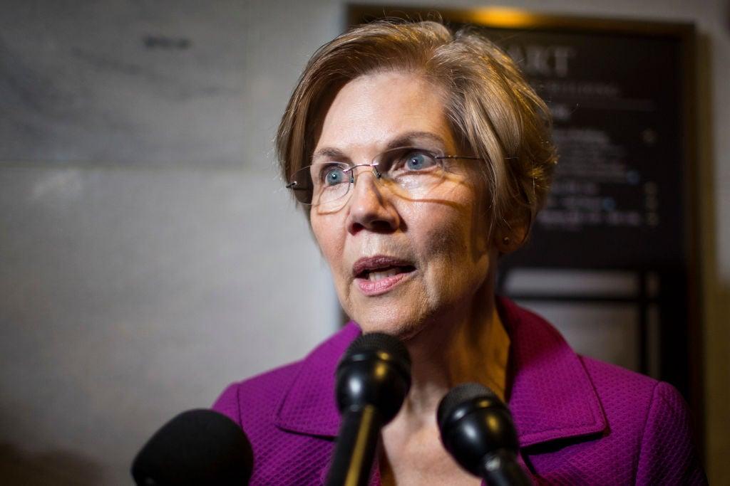 Warren, seen in closeup speaking into reporters' microphones.