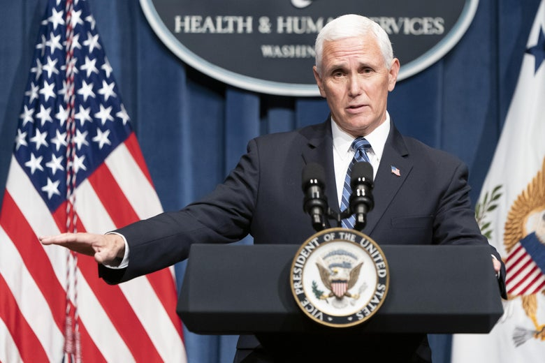 Pence standing at a podium holding his hand out as if to indicate a number is low