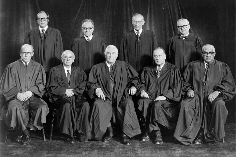 Nine men in robes pose for a photo.