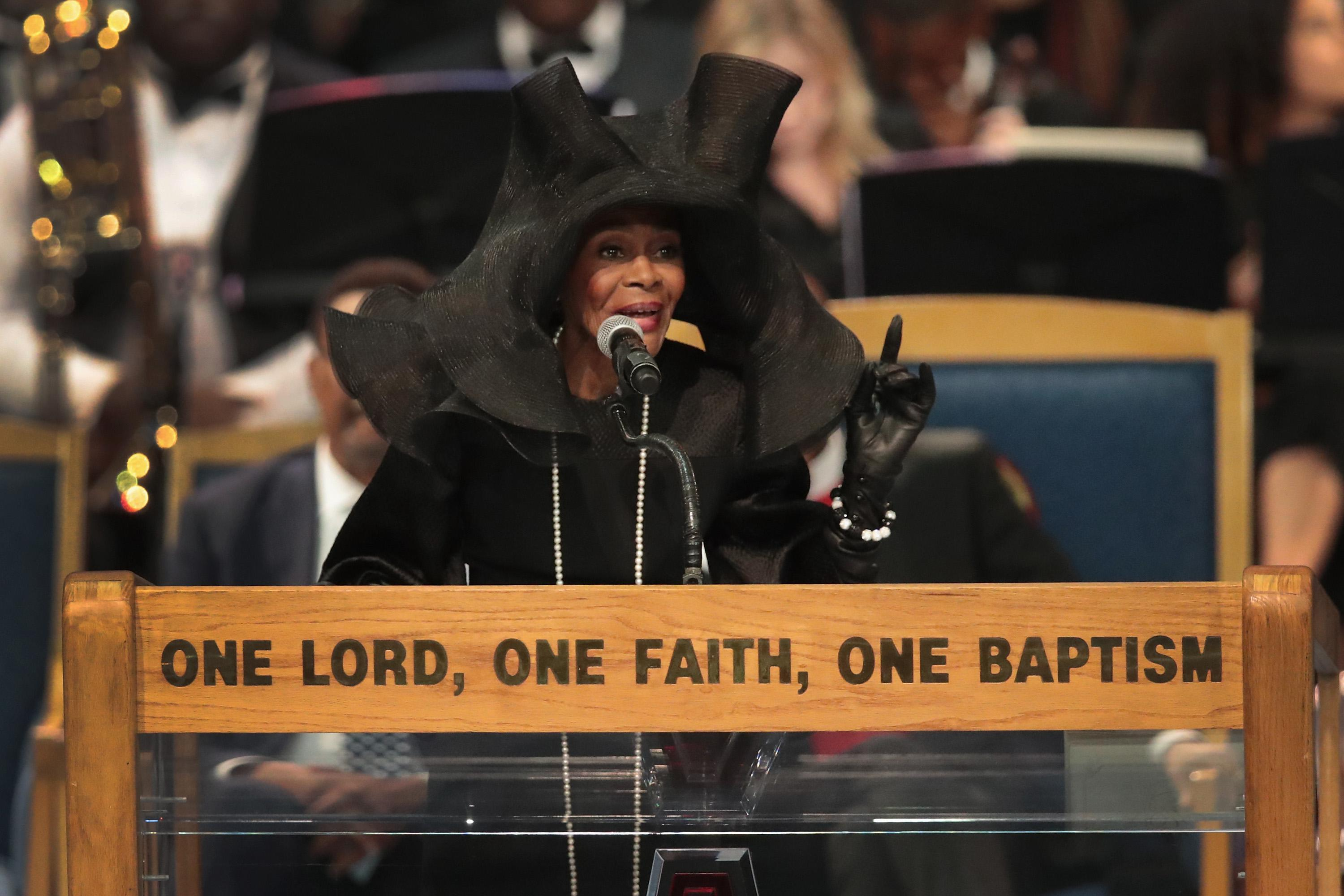 Cicely Tyson speaks at a podium at Aretha Franklin's funeral in a gigantic black floppy hat.