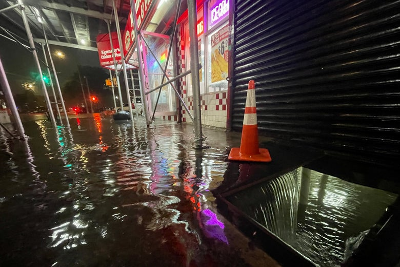 A street view of rain flooding the basement of a Kennedy Fried Chicken fast food restaurant.