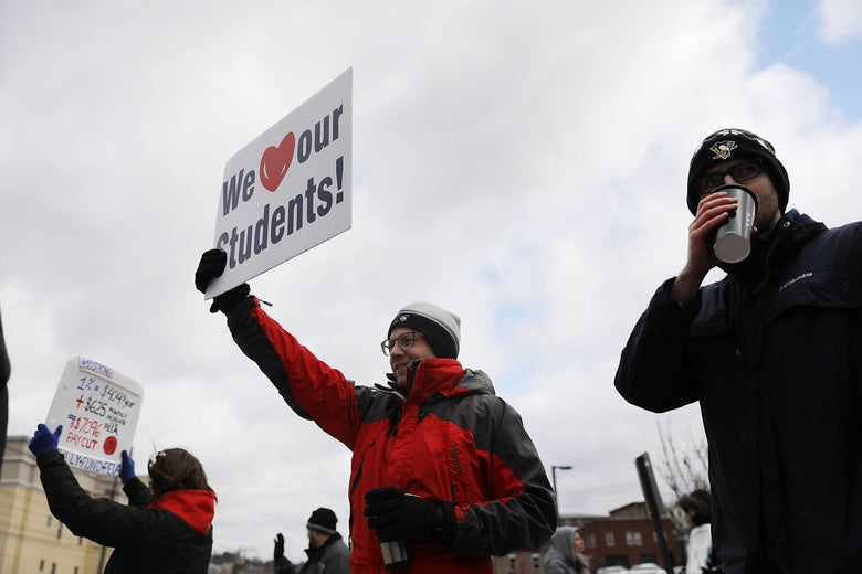 "West Virginia teachers hold signs, saying things like, ""We [heart] our students!,"" as they strike in Morgantown, West Virginia."