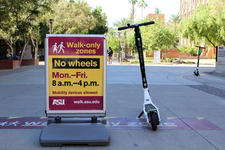 "An electric scooter is next to a sign at ASU that says ""Walk-Only Zones / No Wheels"""