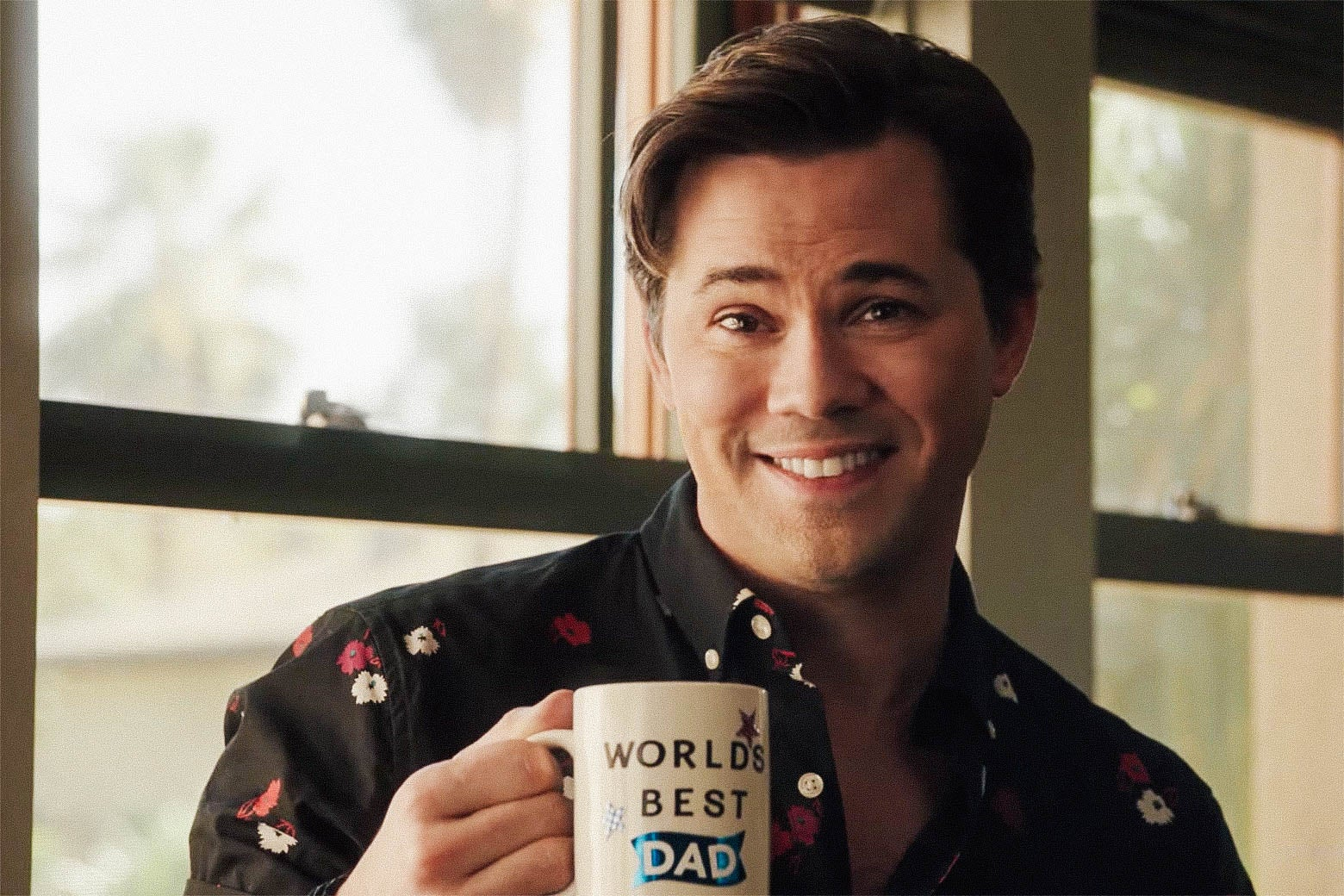 "Andrew Rannells' character holds up a ""World's best dad"" coffee mug."