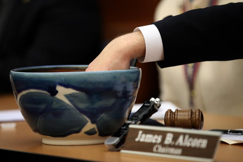 A lawmaker pulls a slip of paper out of a ceramic bowl.